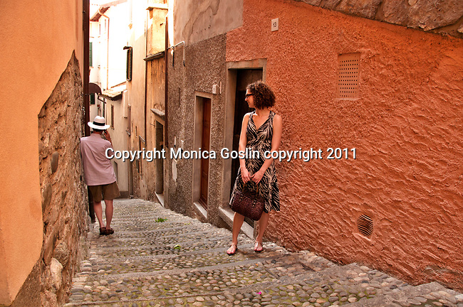 A man with a hat talks on the phone while a woman wearing a black dress looks on; street scene in Bellagio, Italy a town on Lake Como