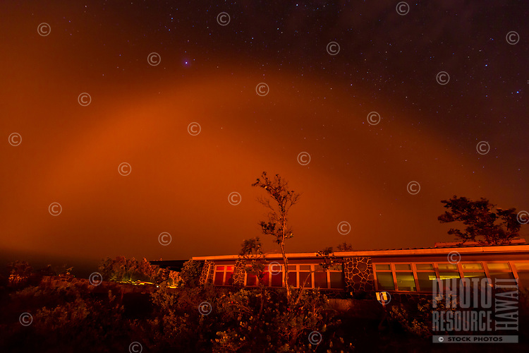 A rare lava bow against a starry sky over Jaggar Museum, Hawai'i Volcanoes National Park, Hawai'i Island. A lava bow occurs when atmospheric moisture brought in by trade winds reflects light from glowing lava. Here, a lava flare-up at Halema'uma'u Crater helped to create this unusual sighting, June 2017.