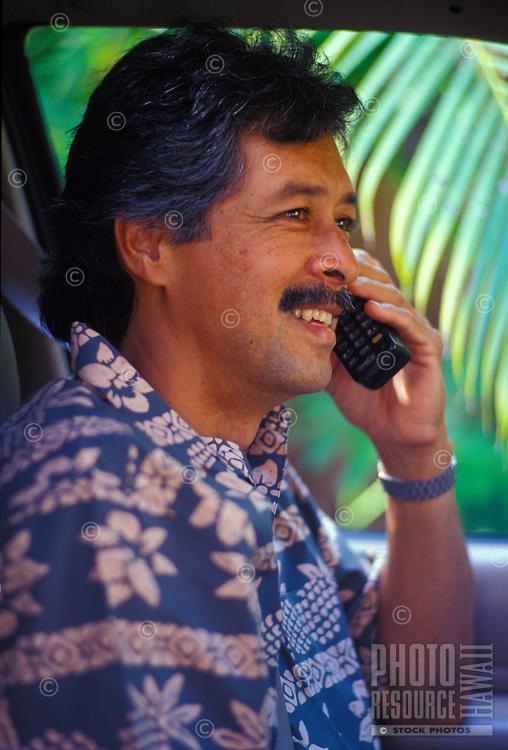Local man talking on cel phone in car