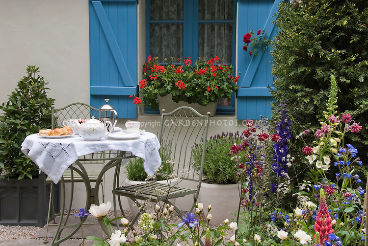 Dining Outdoors In The House Garden Patio With Spring Flowers And Windowbox  Of Geraniiums. Perennial