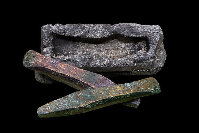 Hittite axe head mould and bronze axe heads. Hittite Period 1600 - 1200 BC. Alaca Hoyuk. Çorum Archaeological Museum, Corum, Turkey. Against a black bacground.