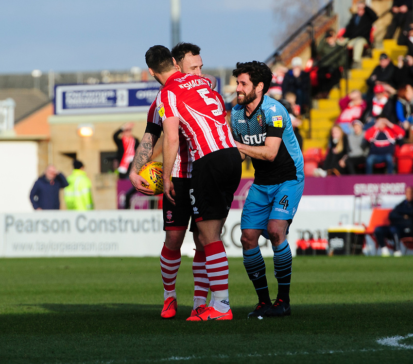 Stevenage's Michael Timlin tries to listen in to a tactical discussion between Lincoln City's Neal Eardley and Lincoln City's Jason Shackell<br /> <br /> Photographer Chris Vaughan/CameraSport<br /> <br /> The EFL Sky Bet League Two - Lincoln City v Stevenage - Saturday 16th February 2019 - Sincil Bank - Lincoln<br /> <br /> World Copyright © 2019 CameraSport. All rights reserved. 43 Linden Ave. Countesthorpe. Leicester. England. LE8 5PG - Tel: +44 (0) 116 277 4147 - admin@camerasport.com - www.camerasport.com