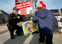 STAFF PHOTO JASON IVESTER --12/17/2014--<br /> Travis Hodges, Springdale firefighter, delivers a toy on Wednesday, Dec. 17, 2014, outside the EOA Children&rsquo;s House in The Pat Walker Center for Children in Springdale. The Springdale Firefighters Association, IAFF Local 3007, parterned with local businesses to collect toys for children in need for Christmas.