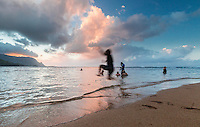At sunset, a family enjoys the warm waters of Hanalei Bay near Princeville Resort, Kaua'i.