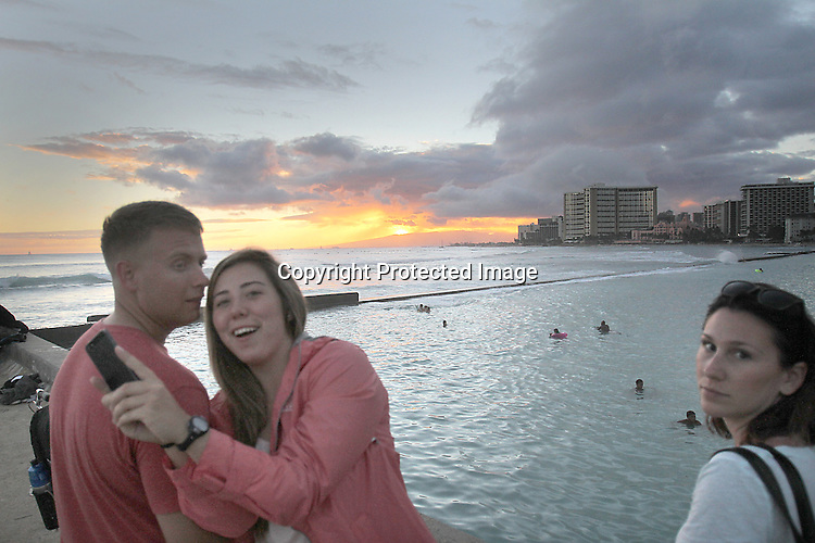"""A young couple attempt to do a """"selfy""""photograph at the the """"Wall"""" at Waikiki."""