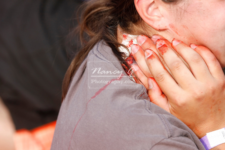 A woman holding her neck injury bleeding with other victims
