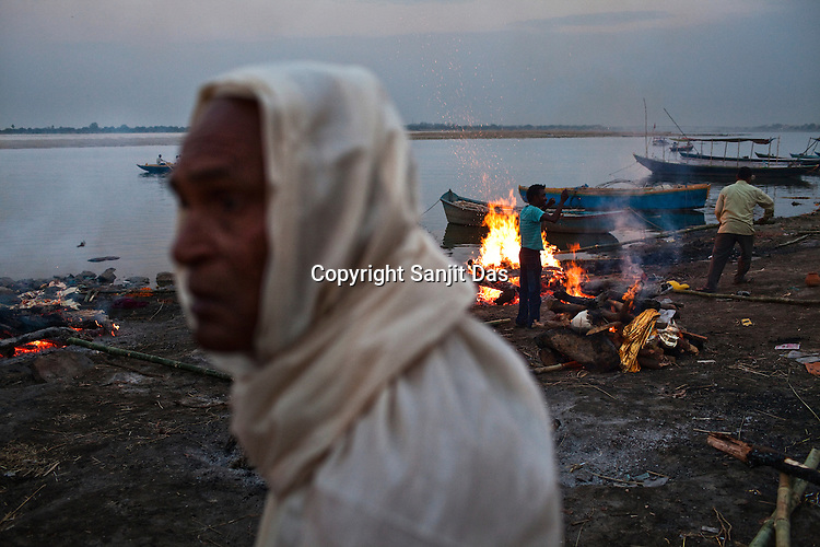 A mourning son (left) looks on while the pyre of his parent burns in the burns in the background at the Harishchandra Ghat in the ancient city of Varanasi in Uttar Pradesh, India. Photograph: Sanjit Das/Panos