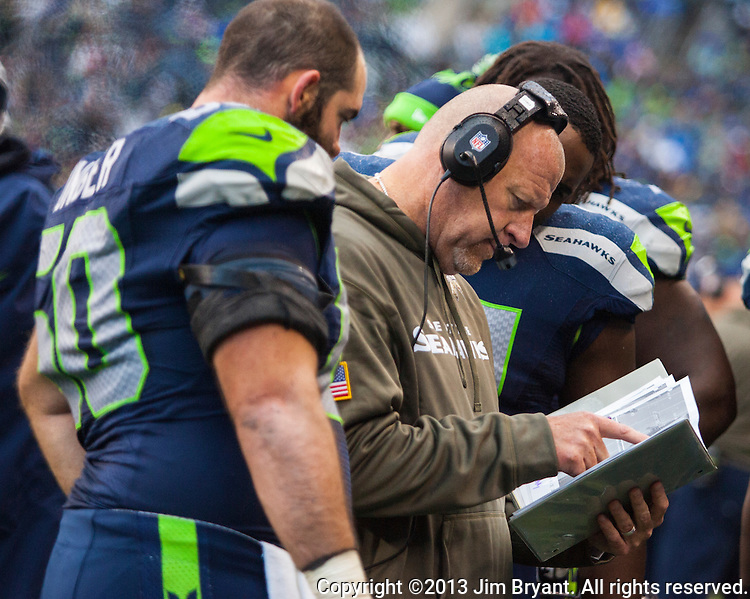 Seattle Seahawks  defensive coordinator Dan Quinn ,center, goes over a log book of Minnesota Vikings defensive lineups with center Max  Unger at CenturyLink Field in Seattle, Washington on  November 17, 2013.  The Seahawks beat the Vikings 41-20.  ©2013.  Jim Bryant. All Rights Reserved.
