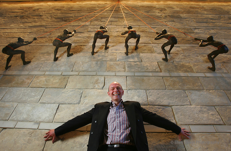 John Schafer, general manager at the Hyatt Regency Denver, stands below some newly-installed art,  six half life-size mountain climbing figures sculpted by local sculptor Bill Starke  on a 35-foot limestone wall in the lobby of the hotel.  The hotel is set to open on December 20, 2005.