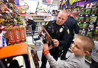 STAFF PHOTO BEN GOFF  @NWABenGoff -- 12/09/14 Shane Brewer, 8, shops with Bentonville police officer Jake Moran during the Bentonville Fraternal Order of Police's annual Shop With a Cop event at the Walmart Supercenter in Bentonville on Tuesday Dec. 9, 2014. Fifty elementary school children from Bentonville schools went shopping with a police officer to find gifts for themselves and their family.