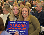 "Westbury, New York, USA. January 15, 2017. Sisters hold sign ""Thanks to the ACA 939,000 NEW YORKERS have gained health Insurance since 2010""  at the ""Our First Stand"" Rally against Republicans repealing the Affordable Care Act, ACA, taking millions of people off health insurance, making massive cuts to Medicaid, and defunding Planned Parenthood. It was one of dozens of Bernie Sanders' rallies for health care nationwide that Sunday."