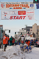 Musher Tom Thurston and Iditarider Aaron Meyer.leave the 2011 Iditarod ceremonial start line in downtown Anchorage, Alaska