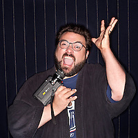 "Kevin Smith, Film Director, photographed in London. Kevin Patrick Smith (born August 2, 1970) is an American screenwriter and director, as well as a comic book writer, author, and actor. He directed Clerks, Clerks II, Mallrats, Dogma, Chasing Amy,  Jay and Silent Bob Strike Back, Jersey Girl, and Zazk and Miri make a Porno. He is also the co-founder, with Scott Mosier, of View Askew Productions and owner of Jay and Silent Bob's Secret Stash comic and novelty store in Red Bank, New Jersey. He hosts a weekly podcast with Scott Mosier known as SModcast. Kevin Smith is known for participating in long, humorous Q&A sessions that are often filmed for DVD release, beginning with An Evening with Kevin Smith. His films are often set in his home state of New Jersey, and while not strictly sequential, they do frequently feature crossover plot elements, character references, and a shared canon in what is known by fans as the ""View Askewniverse"", named after his production company View Askew Productions. He has produced numerous films and television projects, including Clerks, Dogma, and Zack and Miri Make a Porno."
