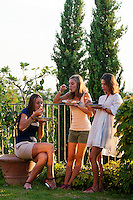 Young women enjoying food during the outdoor party at Maddalena Caruso's home