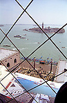 View of Venice and map over the busy traffic of the Giudecca Canal to San Giorgio from behind the wire mesh of the Campanile (tower)