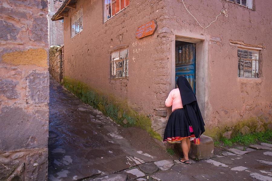 TAQUILE ISLAND, PERU - CIRCA APRIL 2014: Woman in typical street in of Taquile Island, in Lake Titicaca, Peru.