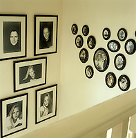 Two collections of framed black and white family portraits adorn the stairwell