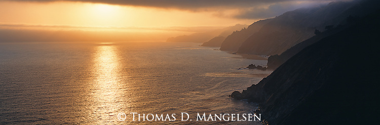 The setting sun silhouettes the Big Sur coast in California, coloring the sky and waves.