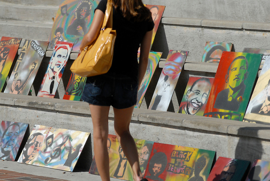 24 Aug 08: A woman browses artwork depicting democratic presidential candidate Barack Obama. Hundreds of vendors have goods available for purchase the week of the Democratic National Convention in Denver, Colorado.