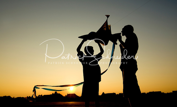 Silhouetted boys prepare to fly their kites at sunset.
