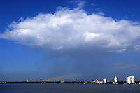 Rick Wilson Photo--A small rainbow appears beneath a lone rain cloud in otherwise clear skies over the St Johns River in Jacksonville, Florida.