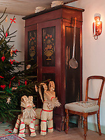 A pair of straw reindeer wrapped in red ribbon stands beside a Christmas tree and an antique cupboard in a corner of the dining room
