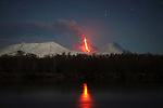 Nighttime Eruption of Kliuchevskoi (Klyuchevskoy) Volcano, Kamchatka, Russia. Ash cloud and lava flow are produced by the snow covered conical stratovolcano. Kamen volcano is seen on right. Lava reflects in Kamchatka river.