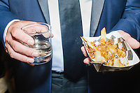 A man holds a glass of ginger ale and a plate of poutine in the Johnnie Walker tent at the MSNBC After Party at the United States Institute of Peace in Washington, DC. The party followed the annual White House Correspondents Association Dinner on Saturday, April 30, 2016. The party continued until about 3 AM on Sunday, May 1, 2016.