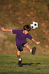 Boy kicking a soccer ball in the early evening sun