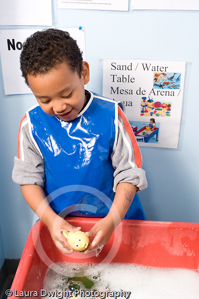 Education Preschool 4-5 year olds smiling boy playing with soap bubble at water table vertical wearing smock