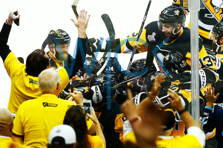 Nick Bonino #13 of the Pittsburgh Penguins jumps on the pile of teammates following the game-winning goal in overtime by Conor Sheary #43 of the Pittsburgh Penguins against the San Jose Sharks during game two of the Stanley Cup Final at Consol Energy Center in Pittsburgh, Pennslyvania on June 1, 2016. (Photo by Jared Wickerham / DKPS)
