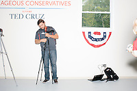 A candidate tracker sets up his equipment before Texas senator and Republican presidential candidate Ted Cruz speaks to a crowd at the kick-off event at his New Hampshire campaign headquarters in Manchester, New Hampshire. The tracker was removed from the headquarters before Cruz arrived.