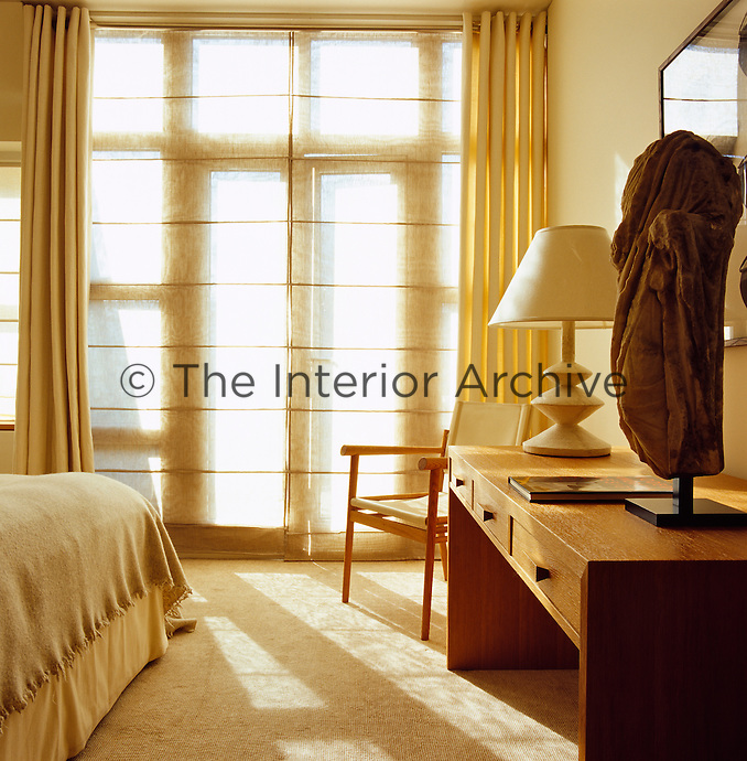 The lined linen curtains combined with translucent blinds create a light and airy mood in the bedroom