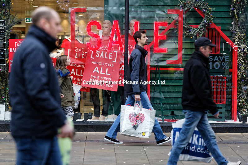"""Last minute Christmas shoppers walk past a """"Sale"""" sign outside Next store in Oxford Street, Swansea, Wales, UK. Monday 24 December 2018"""