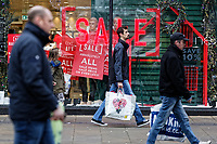 "Last minute Christmas shoppers walk past a ""Sale"" sign outside Next store in Oxford Street, Swansea, Wales, UK. Monday 24 December 2018"