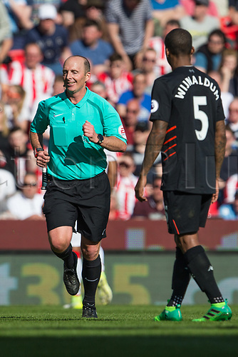 April 8th 2017, bet365 Stadium, Stoke on Trent, Staffordshire, England; EPL Premier League football, Stoke City versus Liverpool; A smiling referee Mike Dean jogs past Wijnaldum of Liverpool