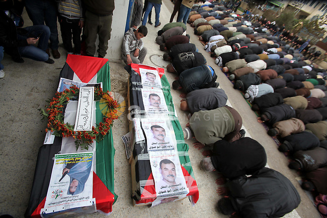 Palestinians pray on the coffins containing the remains of Ayat al-Akhras and Daoud Abu Swai during their funeral in Deheishe refugee camp in the West Bank town of Bethlehem February 3, 2014. Last month, Israel began to exhume the remains of a number of Palestinian militants, including al-Akhras and Swai, to return them to their families for burial in a move that could help ease some tension between the adversaries. Al-Akhras and Swai, blew themselves up in two separate attacks against Israelis some 12 years ago in Jerusalem. Photo by Mamoun Wazwaz