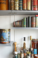 The open shelving in the kitchen displays a collection of early 20th century biscuit tins in the shape of books