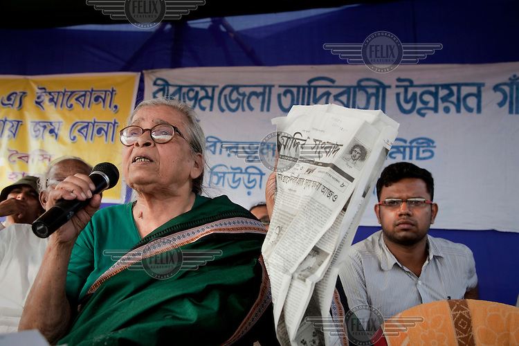 A Mahasweta Devi leads a protest rally by Santal Adavesi tribespeople on the West Bengal / Jharkhand border. They were protesting the destruction of their land as a consequence of the excavation of a stone quarry. Newspaper in hand, Devi attacks the Indian mass media for portraying tribal protests as being connected with the Maoist insurgency instead of being grass roots and unconnected with the Maoists. She is one of India's best-known activists and writers. She has produced both fiction and non-fiction books dealing with the plight of India's poor and dispossessed, especially women and Adivasis (India's indigenous tribes). In addition to her writing, she has led numerous protests and actions against Indian government policies that oppress the poor..