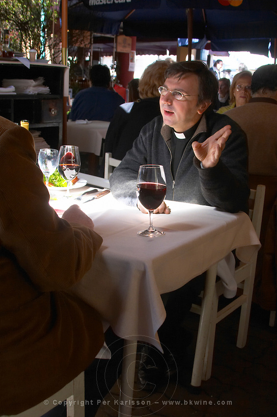A priest in black and collar having lunch and a glass of wine and discussing with another person, in the restaurant El Palenque, the sword fish swordfish, in the Mercado del Puerto, the market in the port harbour harbor where many people go and eat and shop on weekends Montevideo, Uruguay, South America