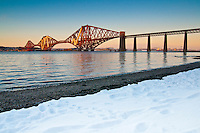 "A (close to) sunset photo of the Forth Rail Bridge, crossing the Firth of Forth between Edinburgh and Fife. This photo was taken during the ""Big Freeze"" (the one at the end of November) of 2010 and snow can still be seen on the shore down to the tide line. Snow can also be seen on the mountains in Fife, across the Forth..The Forth Bridge is an instantly recognisable landmark associated with Scotland and Edinburgh in particular and might be nominated as one of the UNESCO World Heritage Sites in Scotland."