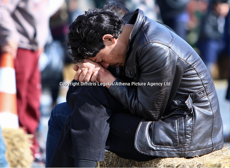 Pictured: A man rests his head on his hands at the road block Tuesday 23 February 2016<br /> Re: Migrants on their way back to Athens have been caught by the blocked off motorway at Tembi, where local farmers have closed off the road, protesting against pension and welfare reforms near Trikala, Greece.