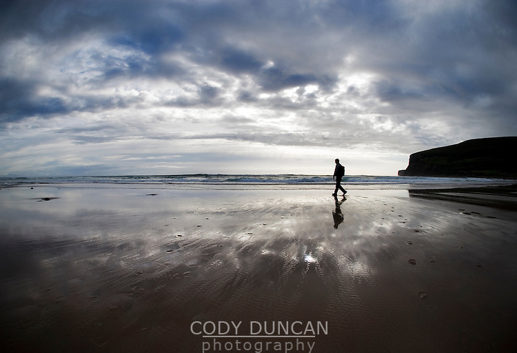 Silhouette of single person walking on empty beach, Scotland