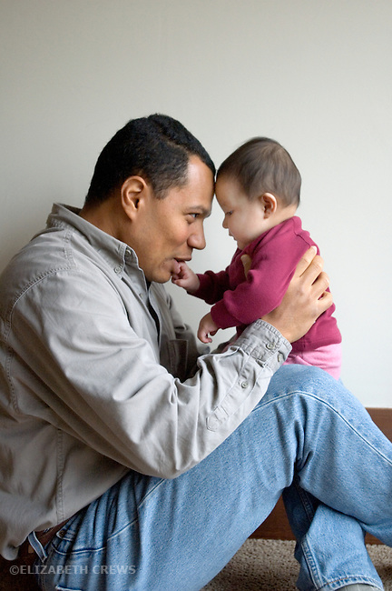 Berkeley CA Adopted baby, none-months-old, in close interaction with father (Cuban)