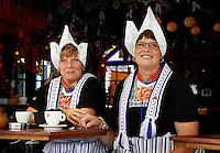 Volendammerdag in Volendam. Inwoners  in klederdracht drinken koffie in een cafe