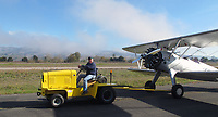 Pilot and aircraft mechanic Roger Willis tows his Stearman to an aircraft display exhibition at the Petaluma Municipal Airport, Petaluma, Sonoma County, California with his natural gas powered tractor.