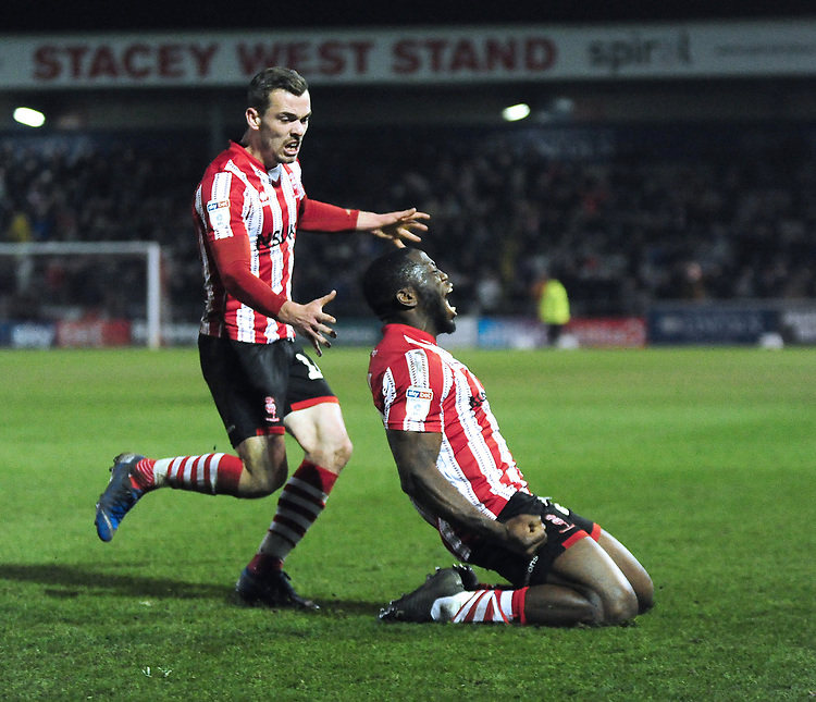 Lincoln City's John Akinde, right,  celebrates scoring his side's equalising goal to make the score with team-mate Harry Toffolo<br /> <br /> Photographer Andrew Vaughan/CameraSport<br /> <br /> The EFL Sky Bet League Two - Lincoln City v Exeter City - Tuesday 26th February 2019 - Sincil Bank - Lincoln<br /> <br /> World Copyright © 2019 CameraSport. All rights reserved. 43 Linden Ave. Countesthorpe. Leicester. England. LE8 5PG - Tel: +44 (0) 116 277 4147 - admin@camerasport.com - www.camerasport.com