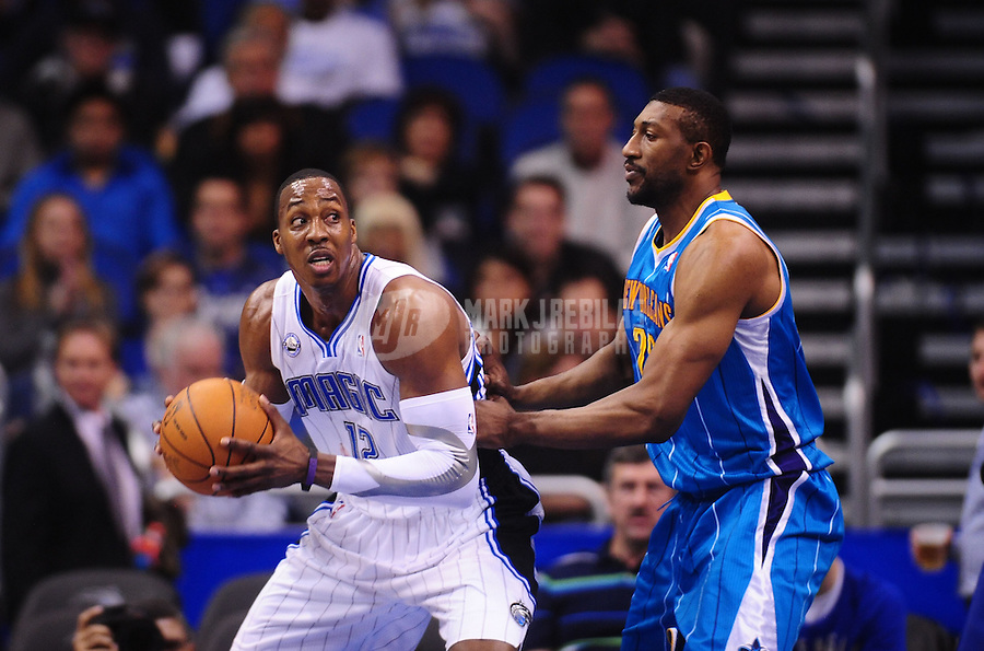 Feb. 11, 2011; Orlando, FL, USA; Orlando Magic center Dwight Howard (12) controls the ball against New Orleans Hornets center Didier Ilunga-Mbenga at the Amway Center. The Hornets defeated the Magic 99-93. Mandatory Credit: Mark J. Rebilas-USA TODAY Sports