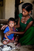 Pramila Tharu, 15, tries to feed her 2 year old toddler Prapti, in Bhaishahi village, Bardia, Western Nepal, on 29th June 2012. Pramila eloped and married at 12 and gave birth to Prapti at age 13. She delivered prematurely on the way to the hospital in an ox cart and her baby weighed only 1.5kg at birth. In Bardia, StC works with the district health office to build the capacity of female community health workers who are on the frontline of health service provision like ante-natal and post-natal care, especially in rural areas. Photo by Suzanne Lee for Save The Children UK