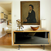 A portrait of Lucienne Day by Henry Carr hangs above a sideboard designed by Robin Day